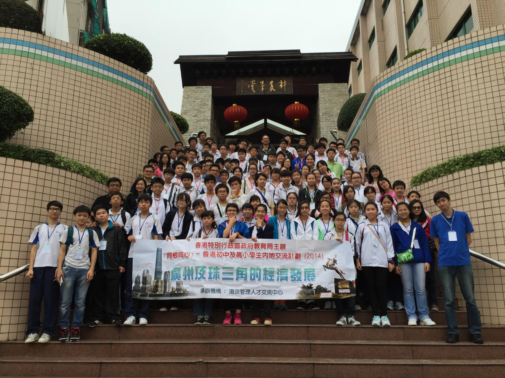 Students and teachers take a photo in front of a Chinese herbal garden.