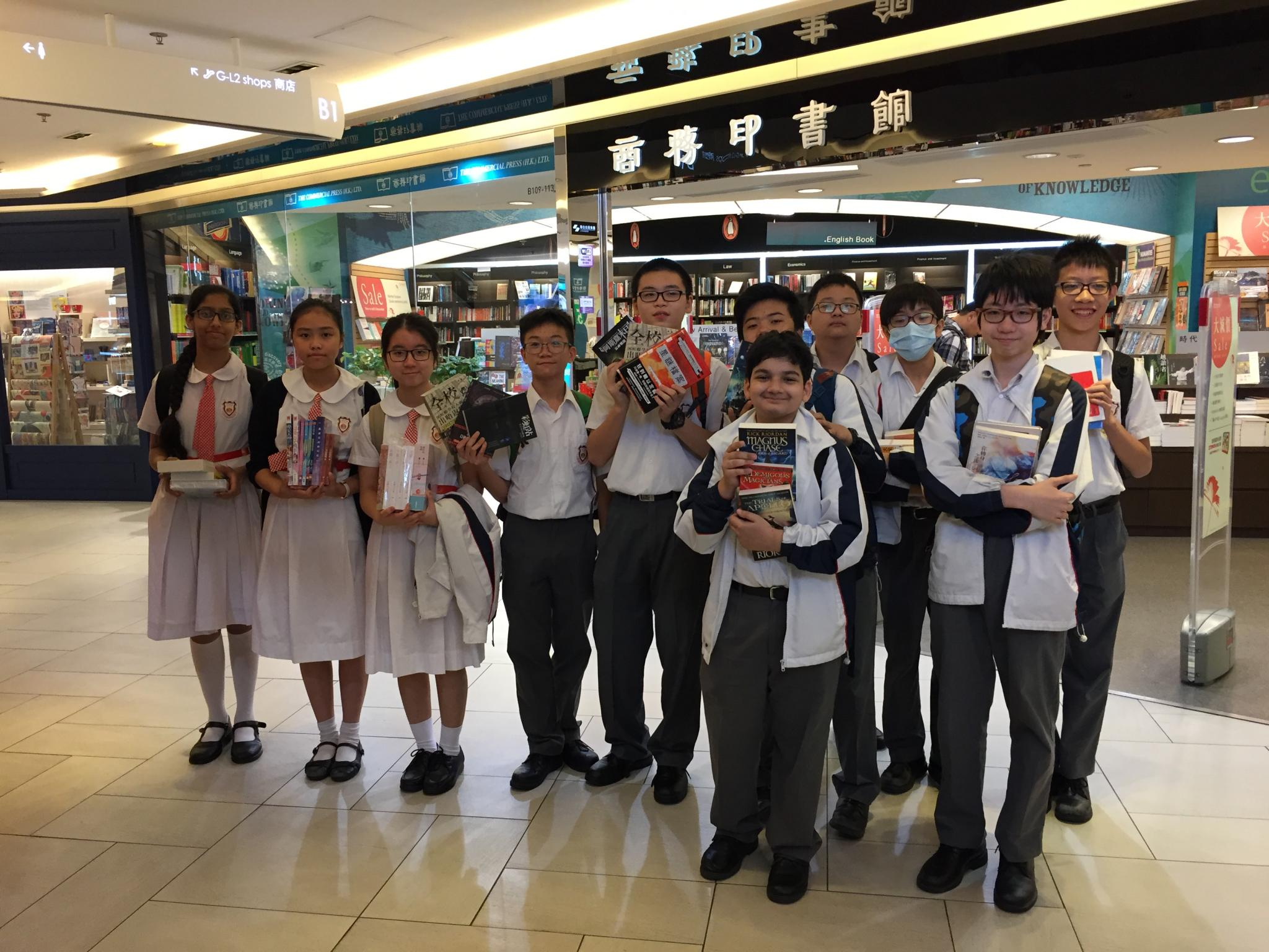 Participants are taking a group photo with their books in front of the book store.