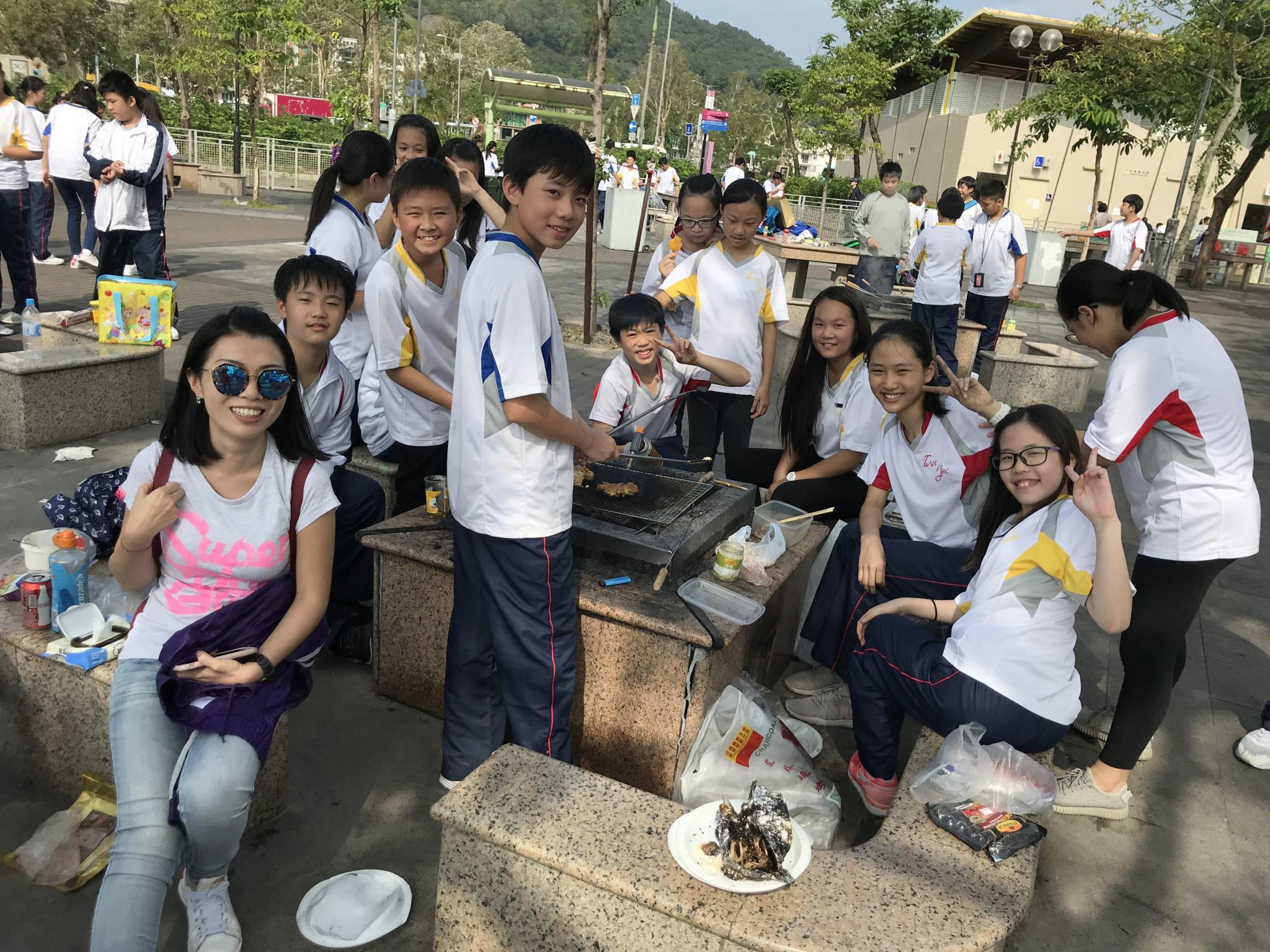 Ms. Lai and students from her class pose for a photo around their barbecue pit.