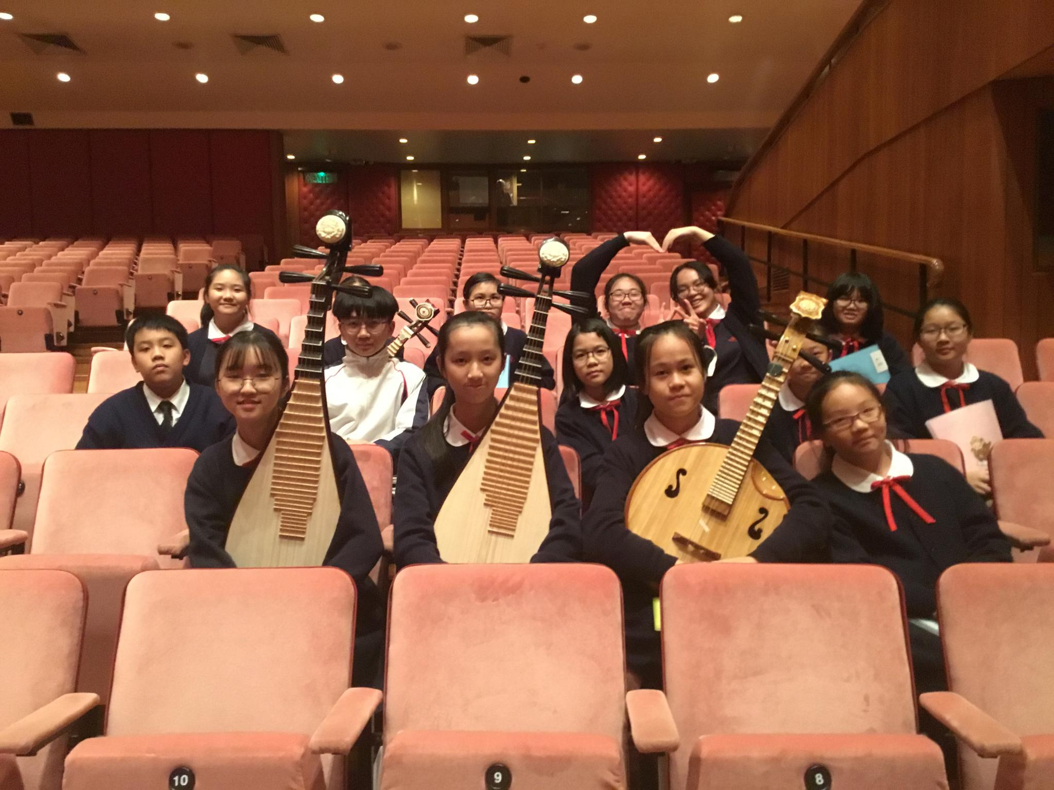 Members of the Chinese Orchestra are posing for a group photo.
