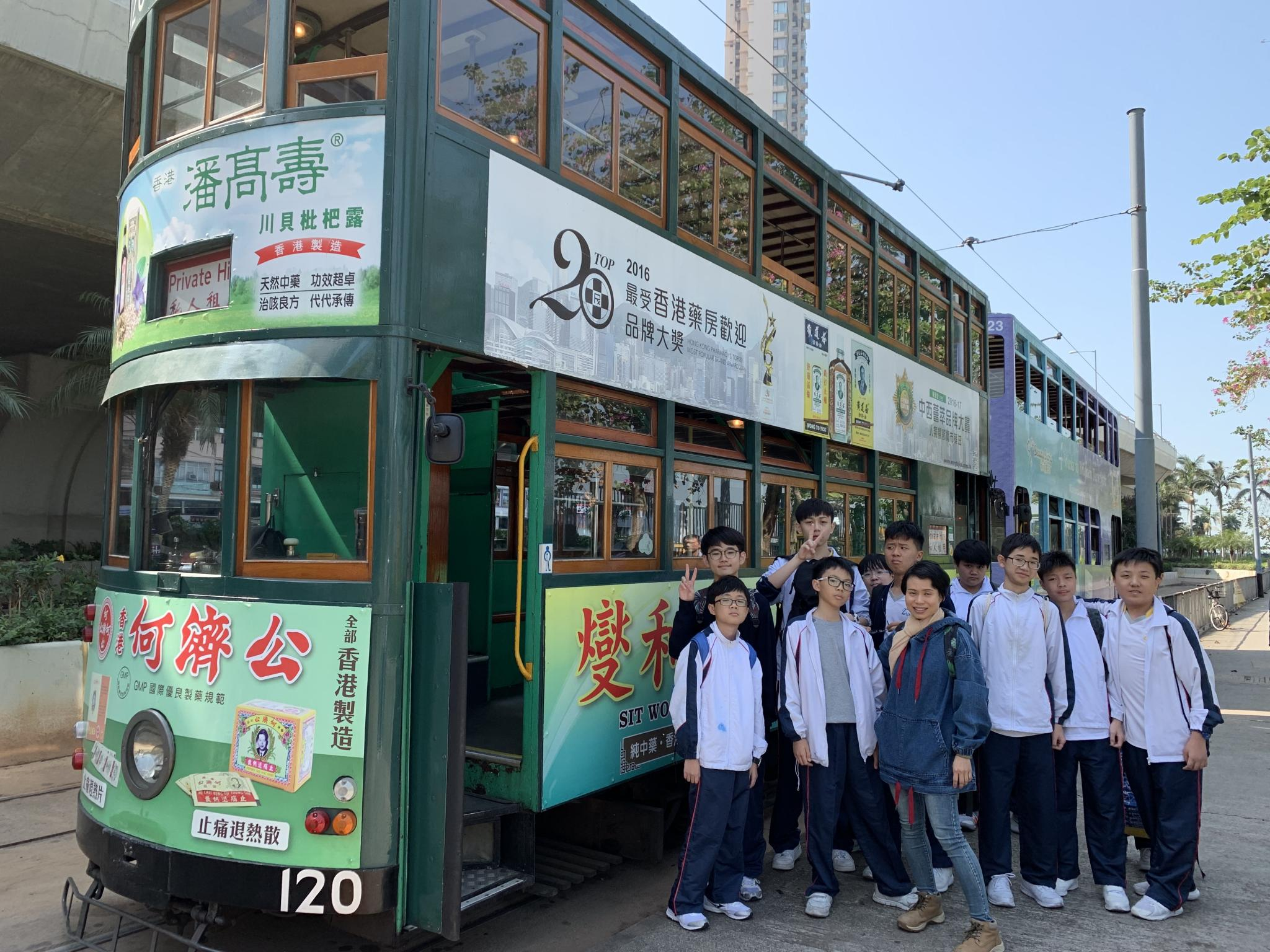 Students pose in front of a tram happily