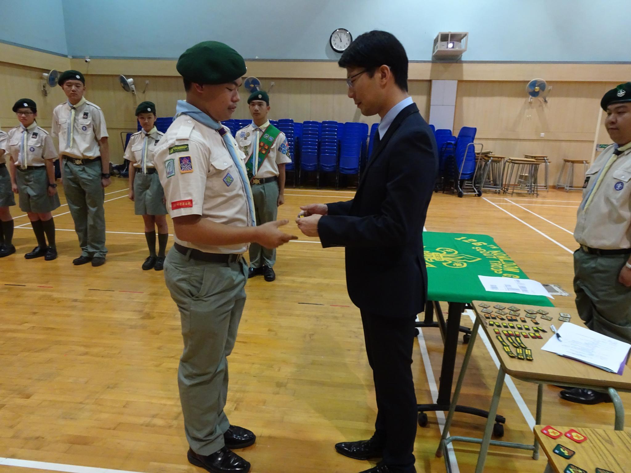Principal Wong Chung Ki was presenting the Senior Patrol Leader Badge to Yung Mo Kin (a KTC student).